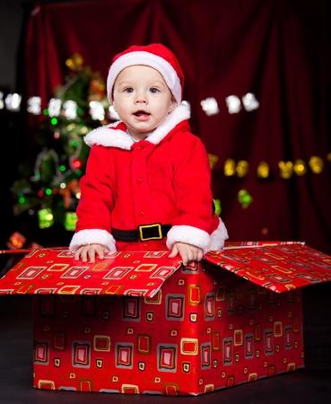 huge christmas tree: Adorable baby boy standing in large Christmas present box Stock Photo