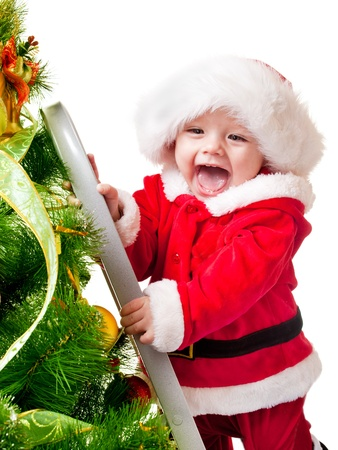 christmas baby: Sweet smiling toddler in Santa hat decorating Christmas tree