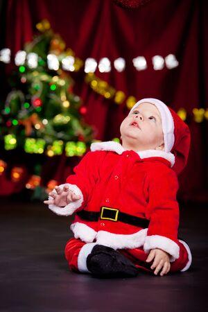 Kid in Santa costume looking up photo