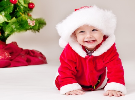 baby christmas: Cheerful toddler in Santa costume crawling