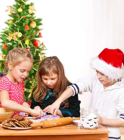 Kids using molds to make Christmas homemade cookies photo