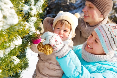 Family decorating fir tree in the park Stock Photo