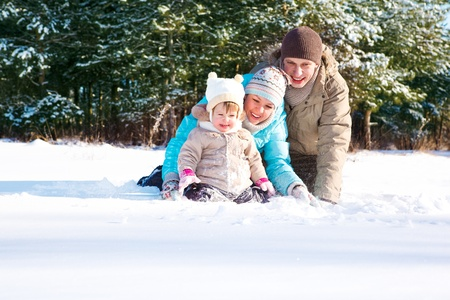 Young cheerful family of three throwing snow in park photo