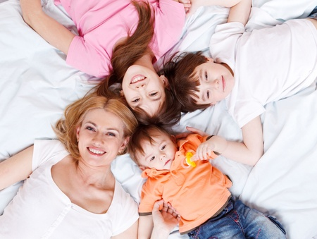 Happy family lying on bed and looking into camera photo
