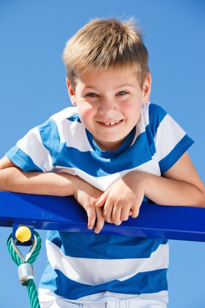 Happy kid climbing up the playground structure elements photo