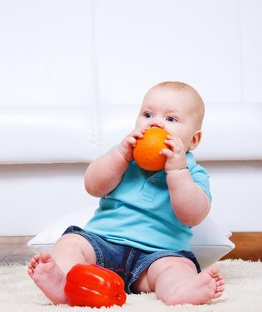 Cute barefoot toddler biting an orange photo