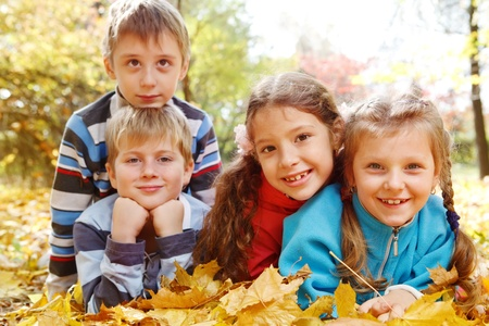 elementary age boys: Beautiful girls and boys lie in autumnal park Stock Photo