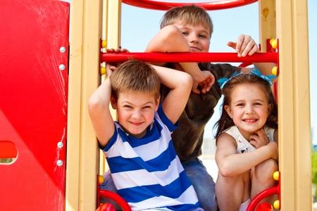 niños en area de juegos: Tres niños de primaria de edad en el patio de recreo