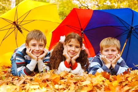 Three children lying under three colorful umbrellas Stock Photo