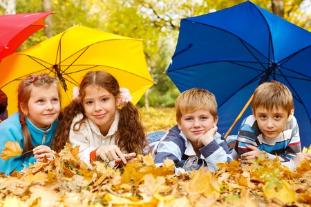 Kids group hiding under colorful umbrellas Stock Photo - 10849342