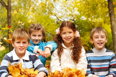 junior student: Portrait of four friendly kids in autumnal park Stock Photo