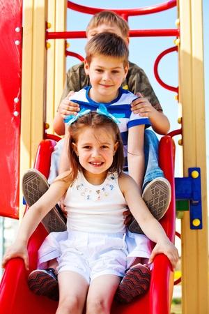 ni�os jugando en el parque: Hermosos hijos en edad escolar en la tolva