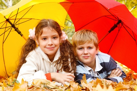 leafage: Boy and girl lying on yellow leafage under two umbrellas