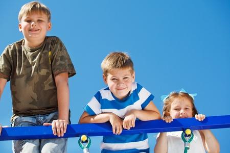 Three kids climbing up the playground net  photo