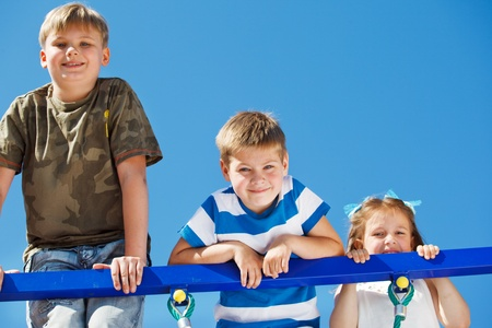 school playground: Three kids climbing up the playground net  Stock Photo