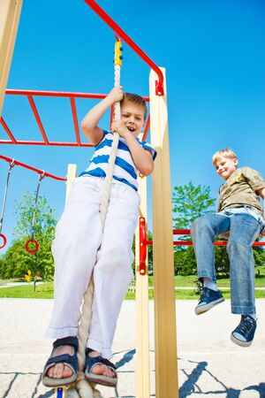 Scared boy trying to swing a rope photo