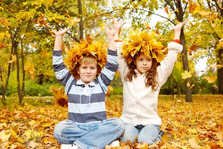 four friends: Two kids in head wreaths catching yellow leaves