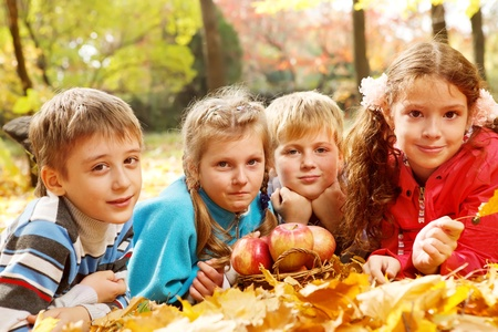 four season: Joyful kids lying on autumnal leaves around apple basket