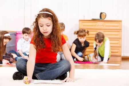 Children group drawing, a girl in red t-shirt sits in front photo