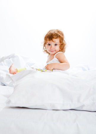 cover girls: Curly toddler girl in bed, looking into camera