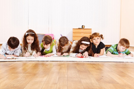 girl drawing: Seven friends lie in roon, drawing  Stock Photo