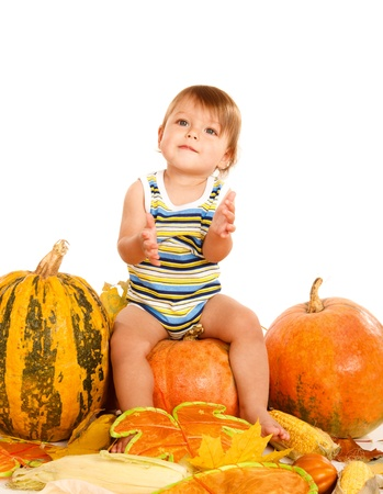 Sweet baby sitting on the pumpkin, over white photo