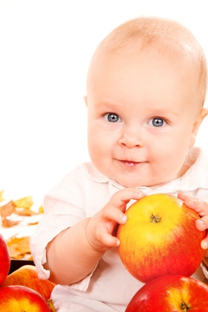 Closeup portrait of baby holding apples in hands photo