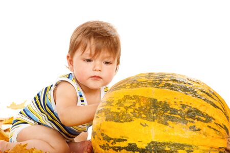 large pumpkin: Toddler playing with large pumpkin Stock Photo