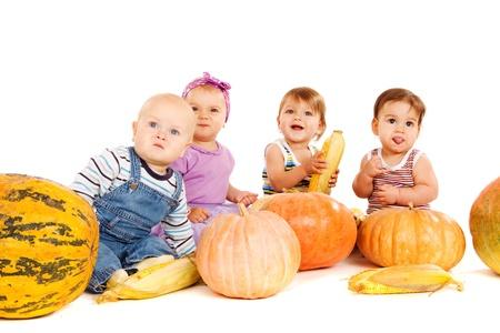 Los bebés se sientan al lado del equipo de la cosecha de otoño