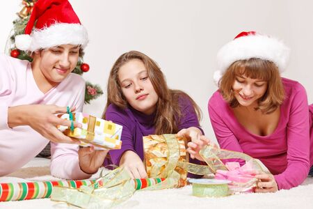 Smiling students in Santa hats packing presents indoors photo