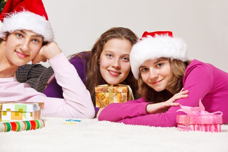 Teenagers lie on floor and packing Christmas presents photo