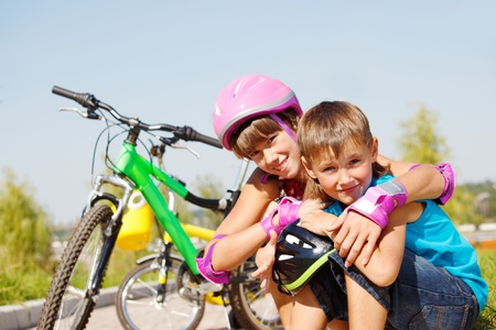 Sportive brother and sister sit beside bikes photo