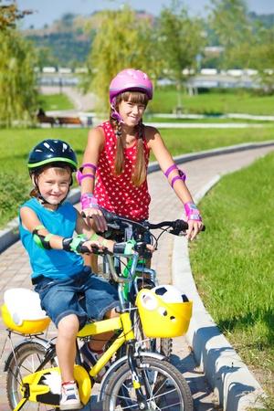 Two children on bikes in park photo
