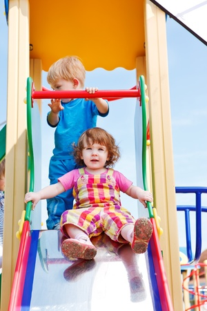 Two toddlers on a chute Stock Photo