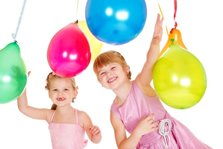 Two laughing kids playing with colorful balloons