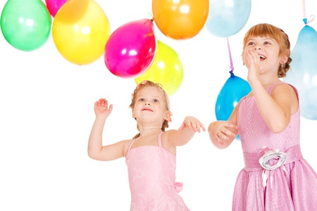 Two sisters playing with birthday balloons, over white photo