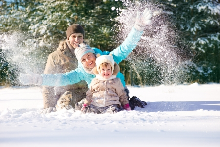 Family throwing snow in park photo