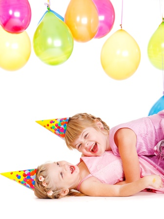Laughing little girls in party hats playing