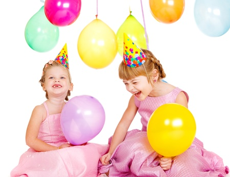 Laughing kids in party hats playing with birthday balloons