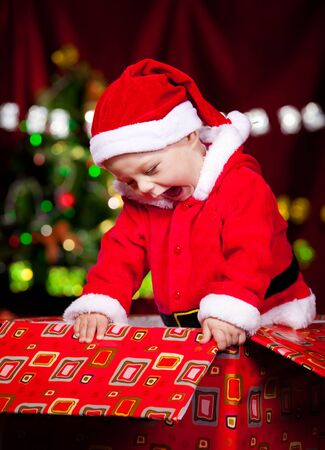 huge christmas tree: Attractive laughing baby in Santa costume