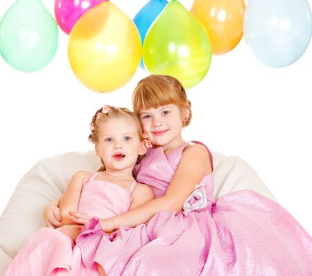Smiling sisters in lovely party dresses photo