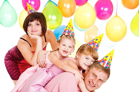 Laughing family of four in birthday party hats photo
