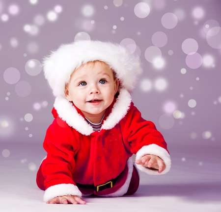 Amazed attractive baby boy in Christmas  costume crawling photo
