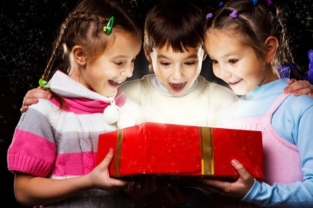 Three excited kids look happily into Christmas gift Stock Photo