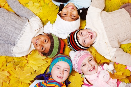 Group of smiling children on autumnal leaves Stock Photo - 11134143
