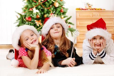 Kids in Santa hats lying on carpet photo