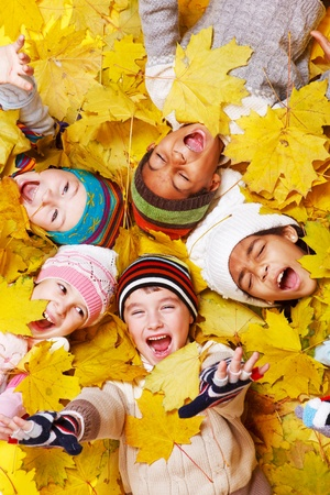 fall fun: Excited children in yellow leaves