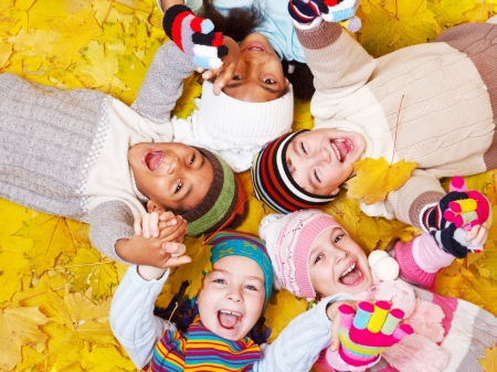 fall fun: Laughing kids on autumnal leaves Stock Photo