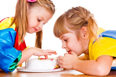 Portrait of little girls eating cake photo