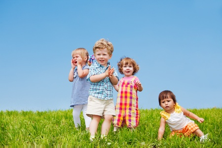 Four emotional toddlers on green grass photo